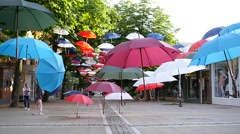 Falling art installation of suspended colored umbrellas  above walking street Stock Footage