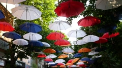 Art installation of suspended colored umbrellas above walking street Stock Footage