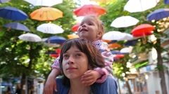 Little kid girl on mother shoulders is happy of art suspended colored umbrellas Stock Footage