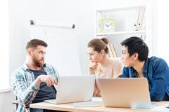Three serious businesspeople having business meeting in office Kuvituskuvat