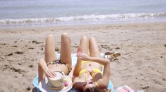 Two young women tanning in their bikinis Stock Footage