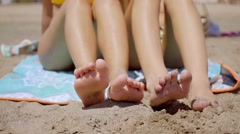 Shapely legs of two young women sunbathing Stock Footage