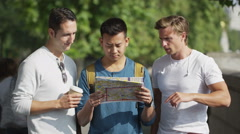 4K Casual male friends looking at map and trying to find their way around city - stock footage