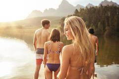 Attractive young woman walking with friends on a jetty Stock Photos