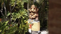 Big statue of hindu deity Ganesha with altar in front of a house, between trees Stock Footage