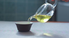 pouring freshly brewed chinese oolong tea from the chahai into the bowl - stock footage