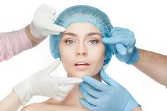 Plastic surgery concept. Doctor hands in gloves touching woman face - stock photo