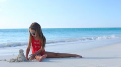 Little girl making sand castle and playing at tropical beach - stock footage