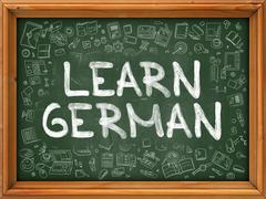 Learn German Concept. Green Chalkboard with Doodle Icons - stock illustration