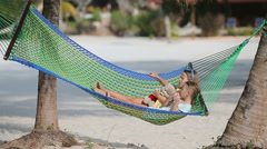 Adorable little girls relaxing in hammock on the beach Stock Footage