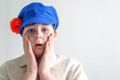 Portrait of surprised boy teenager in Russian national cap with cloves - stock photo