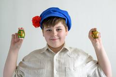 boy in Russian national cap with cloves holding easter eggs - stock photo