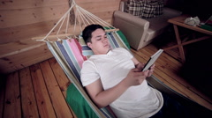 Internet dependent man tired of being on-line, using tablet, lying on hammock - stock footage