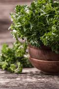 Tied fresh parsley on wooden surface, healthy food Stock Photos