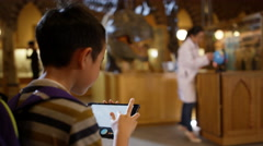 4K Little boy with tablet in museum, looking with fascination at dinosaur - stock footage