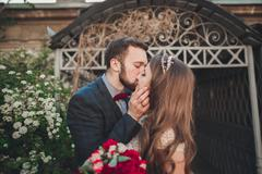 Kissing wedding couple in spring nature close-up portrait Stock Photos