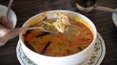 Asian man spoon the hot Thai spicy shrimp soup (Tom Yum Kung) - stock footage