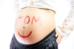 Pregnant mommy expecting son named Tom. - stock photo