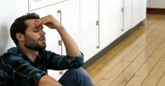 Man is sitting against a wall with a sad expression on his face Stock Footage