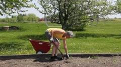 Gardener digging weeds from the garden Stock Footage