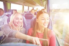 Happy young women riding in travel bus Stock Photos
