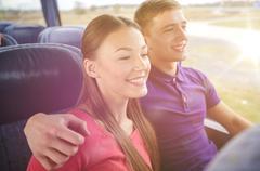 happy teenage couple or passengers in travel bus - stock photo