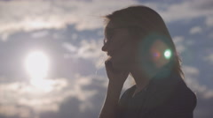 Girl is talking by phone on sky and sun background 4K Stock Footage