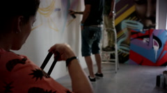 Graffiti artist wearing protective mask and spraying at studio. - stock footage