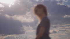 girl with phone is standing on cloudy sky background 4K - stock footage