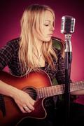 Attractive woman playing acoustic guitar Stock Photos