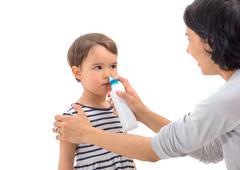 Parent's hand of a girl applies a nasal spray Stock Photos