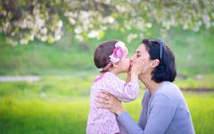 Family, children and happy people concept - happy little girl hugging and kis Stock Photos