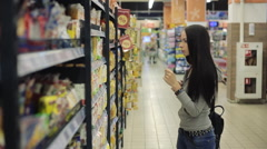 Young pretty girl shopping in a grocery store/supermarket. She looks flour - stock footage