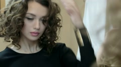 Beautiful curly brunette looks in the mirror Stock Footage