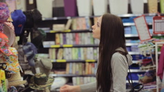 Young happy girl shopping for a hat at store - stock footage