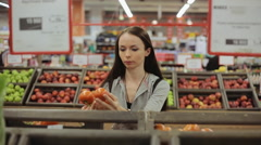 Young pretty girl is choosing tomatoes in a grocery store/supermarket Stock Footage