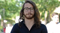 Young man portrait in a park. Middle twenties. Long hair, blue  eyes and glasses - stock footage