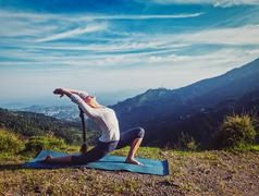Sporty fit woman practices yoga Anjaneyasana in mountains Stock Photos