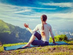 Woman practices yoga asana Marichyasana - stock photo
