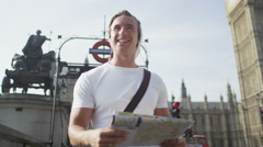4K Casual young man looking at London map and trying to find his way around city - stock footage