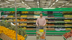 Man with shopping trolley at the supermarket Stock Footage