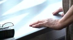 Elderly woman's hands on windowsill - stock footage