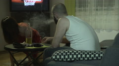 Beaten woman lying in unconscious, man bully sitting, smoking and drinking. Stock Footage