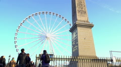 Tourists looking at high Egyptian Luxor Obelisk, huge observation wheel in Paris Stock Footage