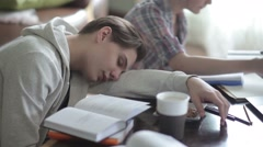Tired student sleeps on the desk. - stock footage