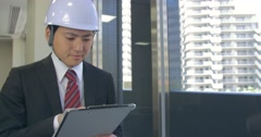 Japanese business man checking safty standards on building project - stock footage
