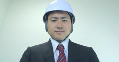 Japanese business man wearing hard hat helmet low angle negative sign  - stock footage