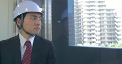 Japanese construction manager looking over site out window and smiles at camera - stock footage