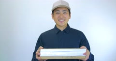 Japanese delivery man gives package to the camera white background  - stock footage