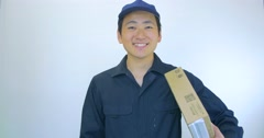 Japanese Delivery man gives thumbs up white background Stock Footage